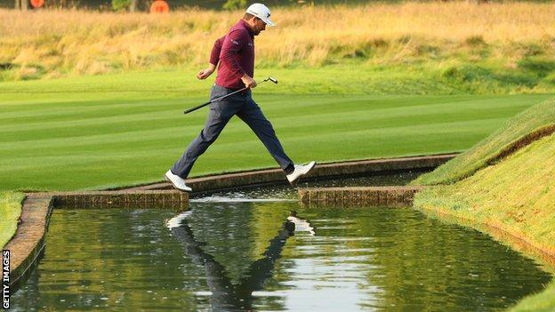 Graeme McDowell skips over the water on the 13th hole at The Grove on Friday