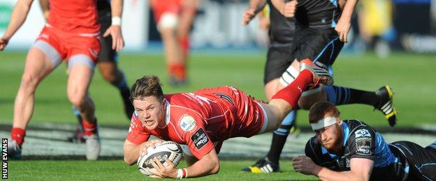 The Scarlets' Steffan Evans is felled by Glasgow's Rob Harley