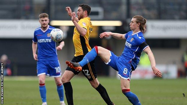 Ben Tozer of Newport County is challenged by Ben Sheaf of Stevenage