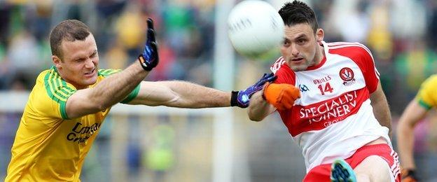 Neil McGee puts the block in on forward Eoin Bradley in the Clones semi-final