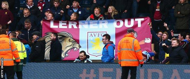 "Aston Villa fans hold a banner at Wycombe declaring ""Lerner Out"""