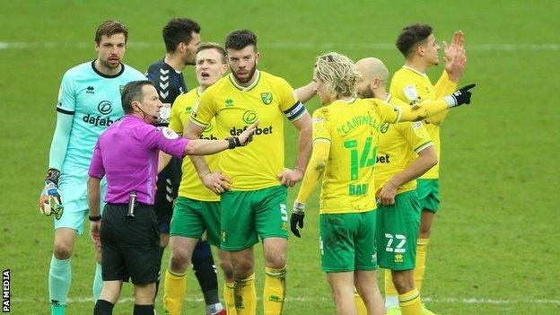 Norwich's players surrounded referee Keith Stroud following his decision to send off Emi Buendia