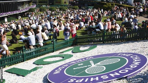Spectators watch the TV screen on Henman Hill at Wimbledon