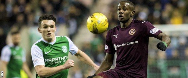 Hibs midfielder John McGinn moves in to tackle Arnaud Djoum