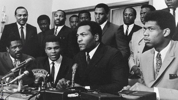 Muhammad Ali and Jim Brown, with a group of prominent black athletes supporting Ali's decision to reject being drafted for the Vietnam War