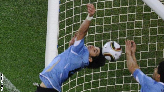 Luis Suarez appears to handle the ball on the line to deny Ghana a late goal at the 2010 World Cup