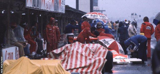 Jochen Mass and James Hunt (both McLaren M23 Fords) in the pits waiting for the rain to stop.