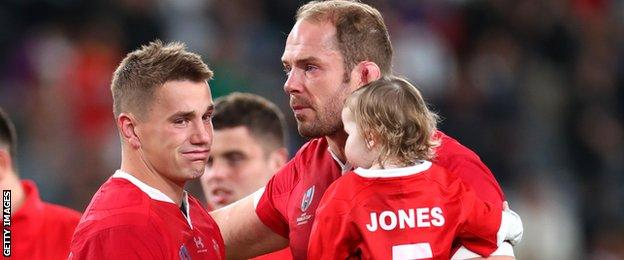 Jonathan Davies is consoled by Alun Wyn Jones, who holds his young daughter Efa in his arms