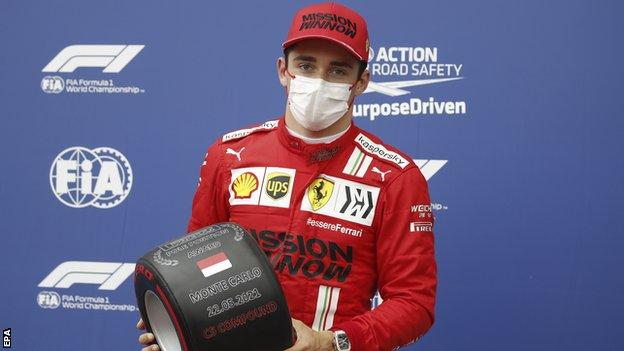 Charles Leclerc holds his pole position award