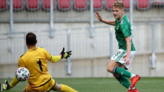 Ali McCann lifts the ball over keeper Henry Bonello to score Northern Ireland's third goal