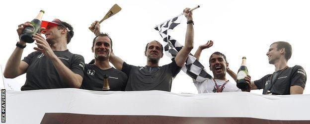 The McLaren team celebrate winning the inter-team raft race