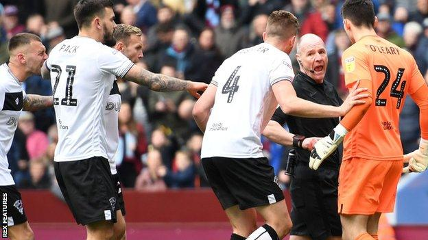 Bristol City players protest after referee Scott Duncan awarded a penalty to Aston Villa