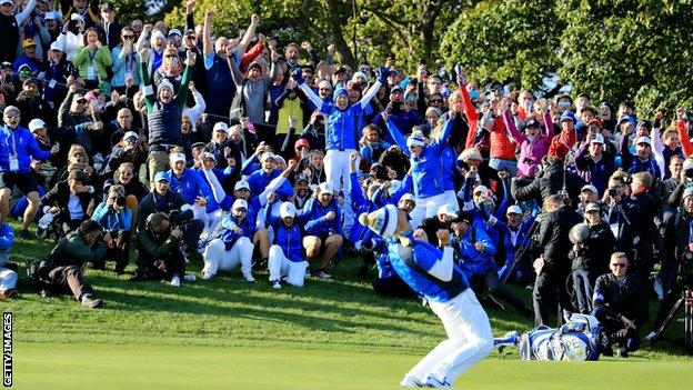 The Europe team rise to their feet along with supporters on the side of the 18th green after Pettersen sinks the winning putt