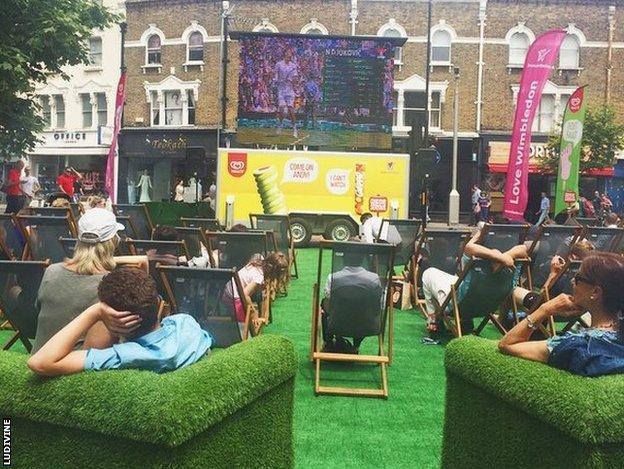 A high street has a Wimbledon big screen to watch