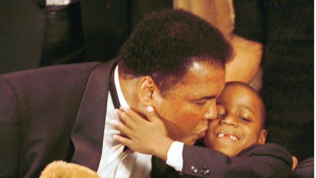 Muhammad Ali holds a UCP bear and kisses Yasin Shelton, a cerebal palsy patien