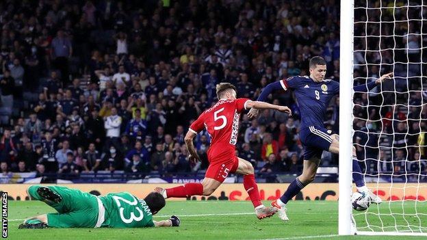 Scotland striker Lyndon Dykes scores
