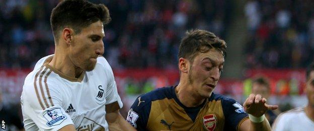 Arsenal's Mesut Ozil (right) battles with Swansea's Federico Fernandez