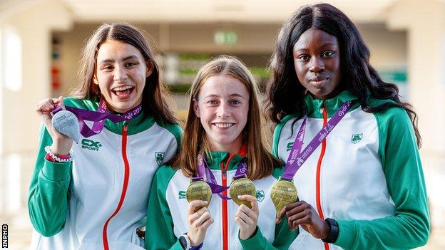 Sophie O'Sullivan, Sarah Healy and Rhasidat Adeleke show off their medals at Dublin Airport after returning from the European Under-18 Championships in Hungary