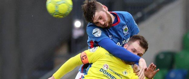 Linfield defender Mark Stafford climbs above Dungannon's Ryan Harpur at Windsor Park