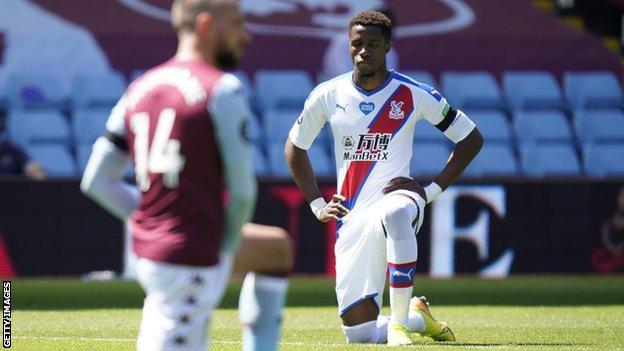 Wilfried Zaha kneeling before Crystal Palace's Premier League game at Aston Villa on Sunday