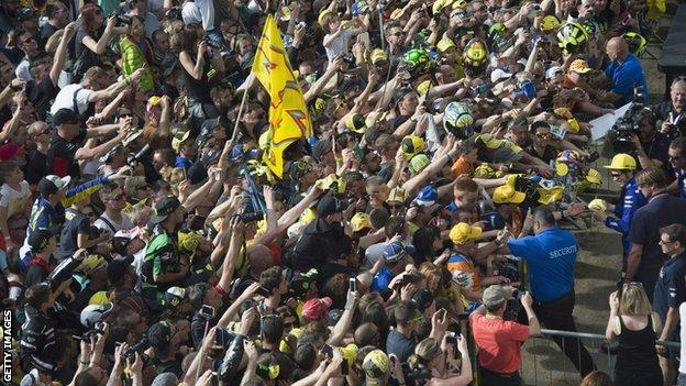 Valentino Rossi is mobbed by loads of fans at a MotoGP racetrack who want an autograph