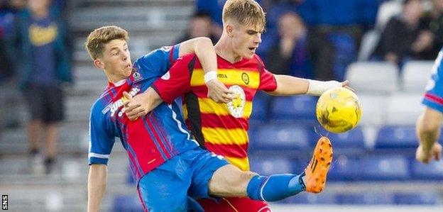 Caley Thistle's Ryan Christie is held off by Thistle's Liam Lindsay