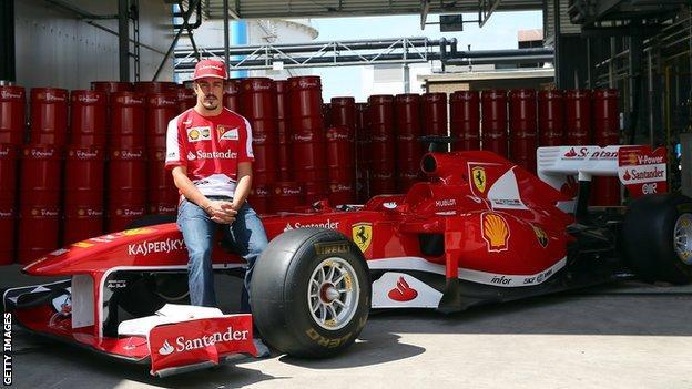 Fernando Alonso poses with the Ferrari car