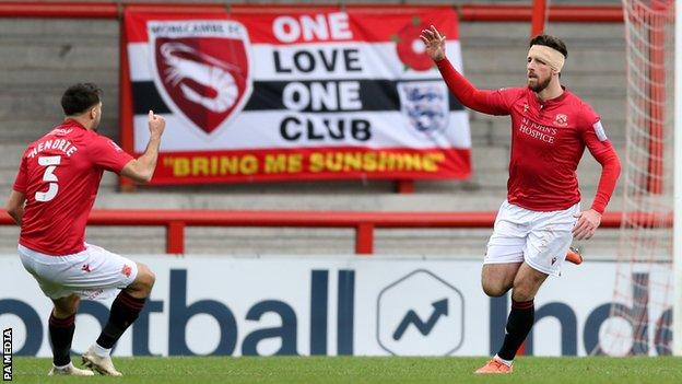 Cole Stockton celebrates scoring Morecambe's first goal against Solihull Moors in the FA Cup second round