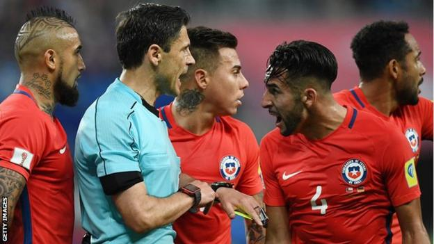 Chile's players surround the referee during the 2017 Confederations Cup final with Germany
