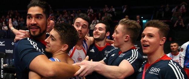 Louis Smith gives team-mate MAx Whitlock a hug as GB celebrate their silver medal