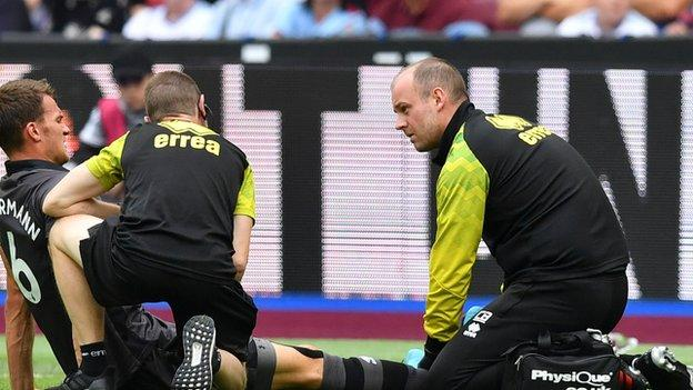 Christoph Zimmermann receives treatment from Norwich physios before being forced off against West Ham