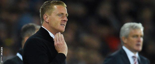Swansea City manager Garry Monk alongside Stoke City boss Mark Hughes
