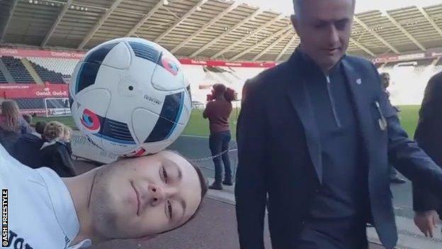 Jose Mourinho walks behind a gent balancing a ball on his head