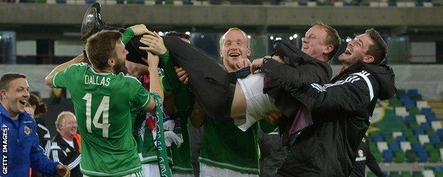 Michael O'Neill is held aloft by Northern Ireland players