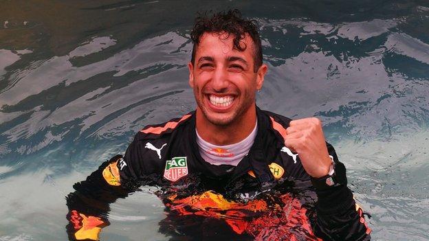 Daniel Ricciardo celebrates in a swimming pool