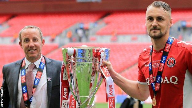 Lee Bowyer and Patrick Bauer celebrate with the League One play-off trophy
