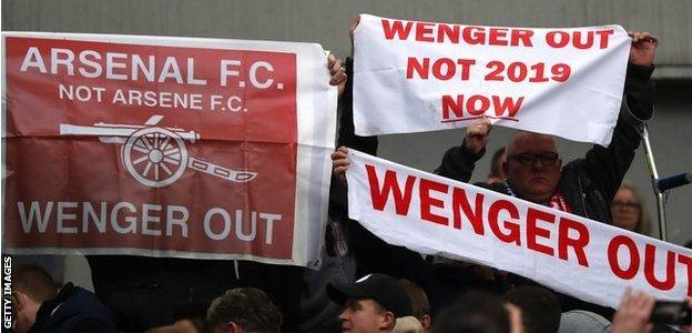 Banners calling for Wenger to leave