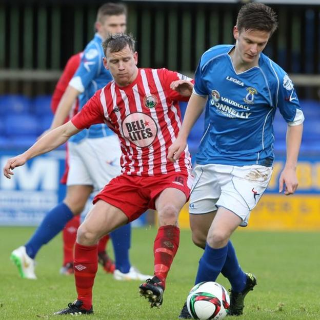 Liam Bagnall of Warrenpoint Town moves in to challenge Dungannon Swifts opponent Douglas Wilson at Stangmore Park