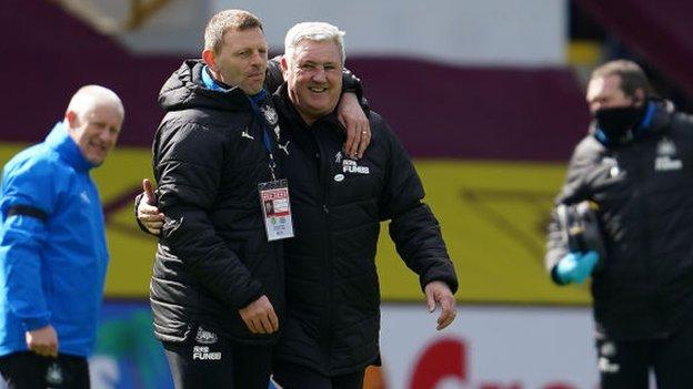 Assistant coach Graeme Jones and manager Steve Bruce celebrate Newcastle's win at Burnley