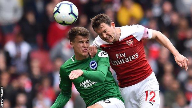 Brighton forward Solly March wins a header against Arsenal right-back Stephan Lichtsteiner