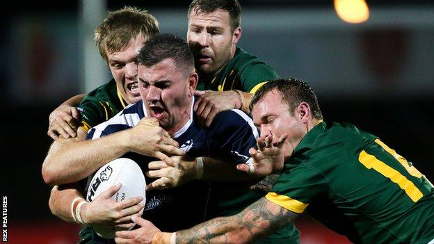 Scotland's Adam Walker is tackled against Australia