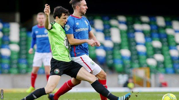 Warrenpoint's Danny Wallace challenges Linfield striker Andrew Waterworth