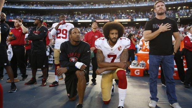 Colin Kaepernick and Eric Reid during the national anthem alongside Nate Boyer