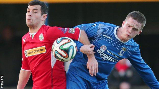 Cliftonville striker David McDaid and Dungannon's Andrew Burns tussle for the ball