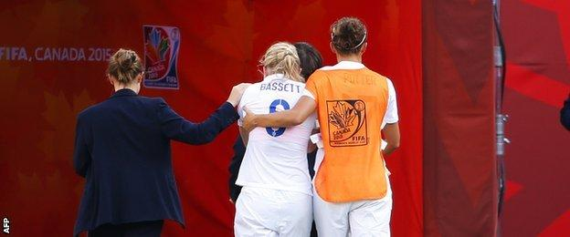 Laura Bassett of England is comforted by team-mates