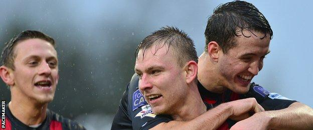 Andrew Mitchell of Crusaders is congratulated after scoring the first goal against Dungannon Swifts
