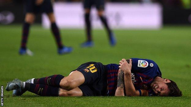 Lionel Messi on the floor in pain holding his right arm