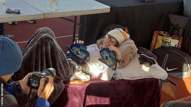 Camille Herron lies down while posing with her Desert Solstice trophies