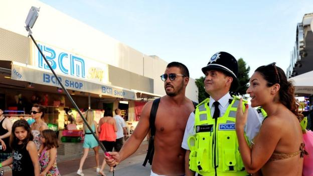 Holidaymakers take a selfie with a British police officer