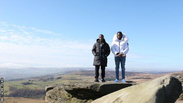 Krept and Konan stand on top of a hill.